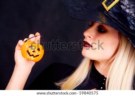 Image of black witch holding pumpkin candle and looking at it - stock photo