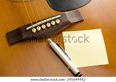 Image of blank paper with pen on old acoustic guitar