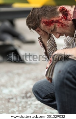 Image of bloody man after road accident - stock photo