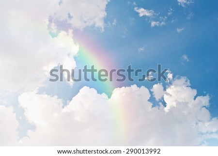 image of blue sky and white clouds with rainbow - stock photo