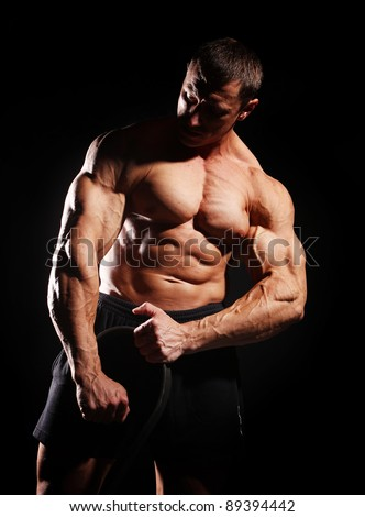 Image of bodybuilder with metal rod, isolated on black - stock photo