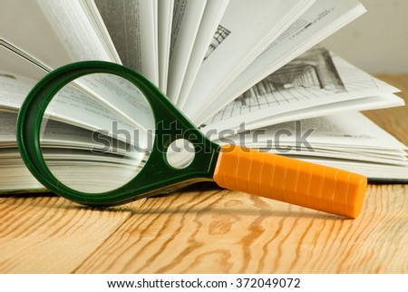 image of book and magnifying glass on a table closeup - stock photo