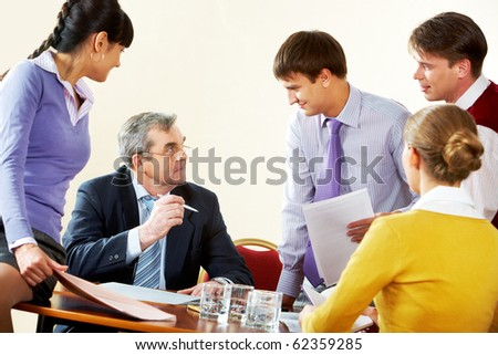Image of boss giving instructions to young businessman during briefing - stock photo