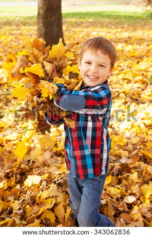 Image of boy playing with autumn leaves in the park, shallow depth of field - stock photo