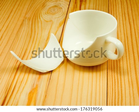 image of broken cup on the wooden table closeup - stock photo