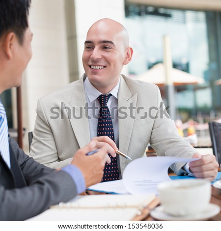 Image of business co-workers having fun while conversation at a cafe on the foreground - stock photo
