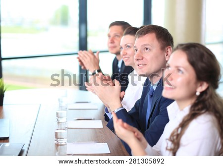 Image of business colleagues applauding in the end of the conference sitting in a line - stock photo