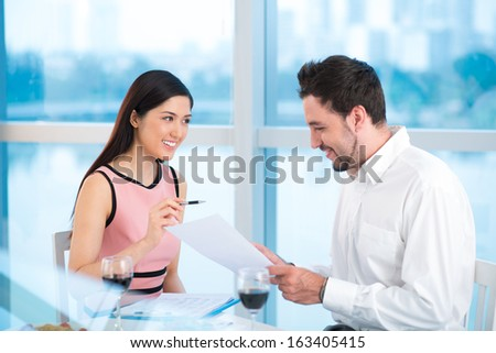 Image of business colleagues sitting at a table and discussing during the lunch