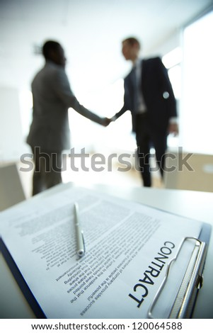 Image of business contract on background of two employees handshaking