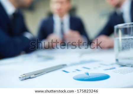 Image of business document and pen at workplace with group of colleagues interacting on background  - stock photo