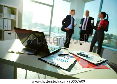 Image of business documents on workplace with three partners interacting on background - stock photo
