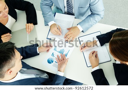 Image of business group discussing business documents at meeting - stock photo