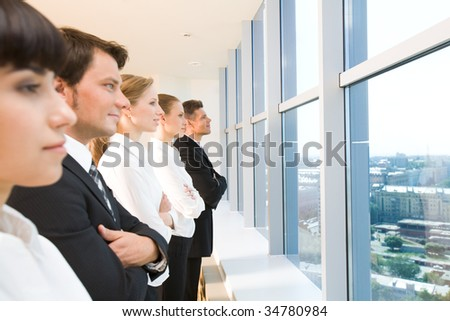 Image of business group standing in line and looking through window - stock photo