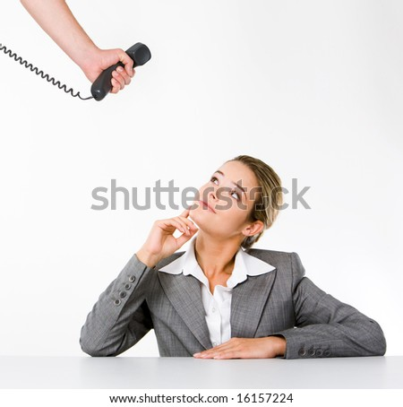 Image of business lady sitting at desk and looking upwards at telephone receiver in bossâ?? hand - stock photo