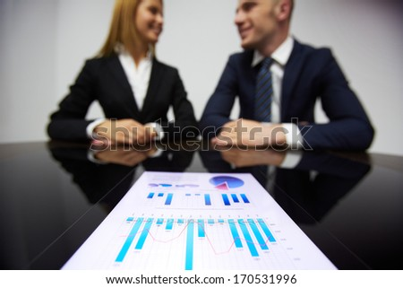 Image of business paper at workplace and business partners on background - stock photo