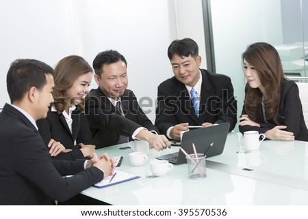 Image of business partners discussing documents and ideas at meeting,asian business team.