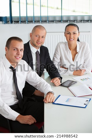 Image of business partners discussing documents and ideas at meeting in office