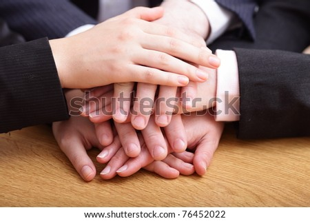 Image of business partners hands on top of each other symbolizing companionship and unity - stock photo
