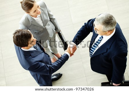 Image of business partners handshaking after striking deal with smart woman near by - stock photo