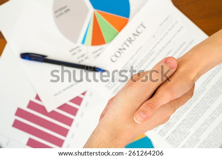 Image of business partners handshaking over business contract - stock photo