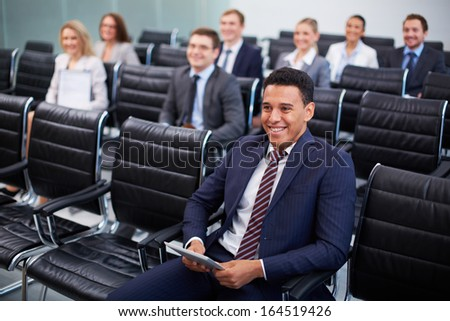 Image of business partners sitting in rows at seminar with smiling man in front - stock photo