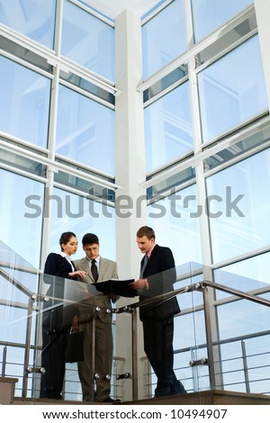 Image of business people interacting on the background of large window - stock photo