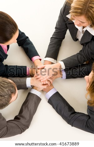 Image of business people keeping hands on top of each other at workplace - stock photo