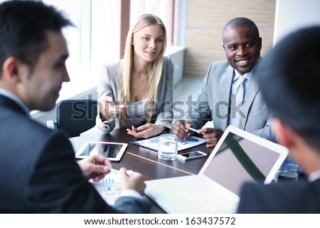 Image of business people listening and talking to their colleague at meeting - stock photo