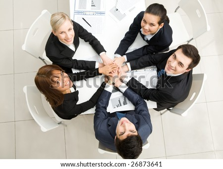 Image of business people with their hands on top of each other and looking upwards - stock photo