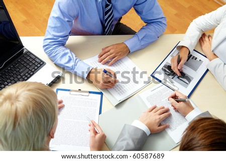 Image of business people working with documents at meeting