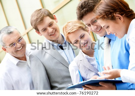 Image of business team looking at paper in male hands at meeting - stock photo