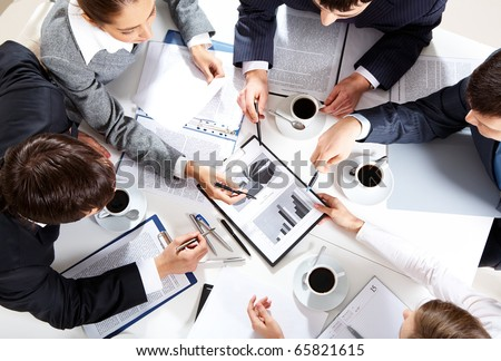 Image of business team sitting at the table and discussing a new project - stock photo