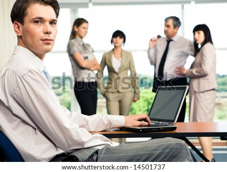 Image of business team with serious leader sitting at the table in front - stock photo