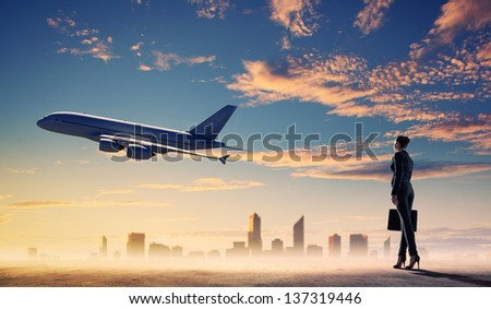 Image of business woman holding suitcase looking at airplane in sky - stock photo