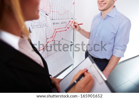 Image of businessman analyzing graph on whiteboard and his colleague - stock photo
