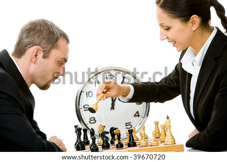 Image of businessman and businesswoman playing in chess with clock on background - stock photo
