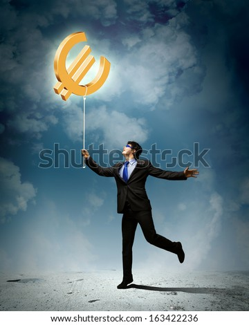 Image of businessman catching euro symbol. Currency concept