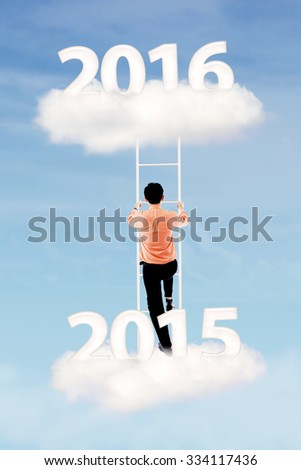 Image of businessman climbing a ladder on the cloud with numbers 2015 and 2016 - stock photo