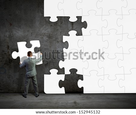 Image of businessman compiling macro white puzzle. Building business - stock photo