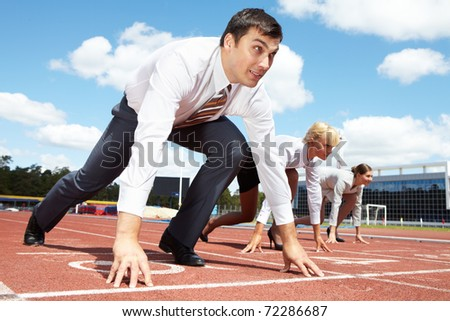 Image of businessman getting ready for race with two females on background - stock photo