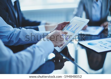 Image of businessman hand pointing at document in touchpad - stock photo