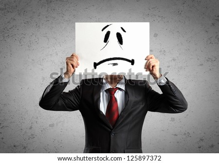 Image of businessman holding drawing of upset face. Conceptual photo
