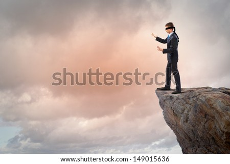 Image of businessman in blindfold standing on edge of mountain - stock photo