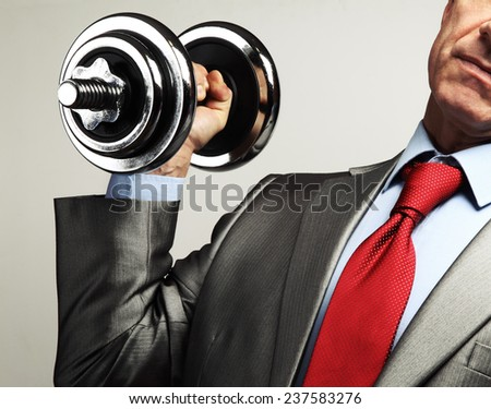 Image of businessman in suit raising dumbbell. Tax burden concept - stock photo