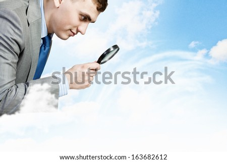 Image of businessman looking in magnifying glass - stock photo