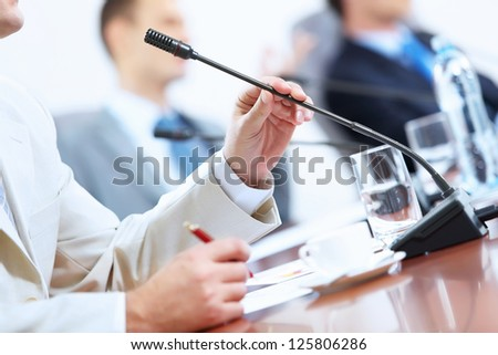 Image of businessman's hands holding microphone at conference