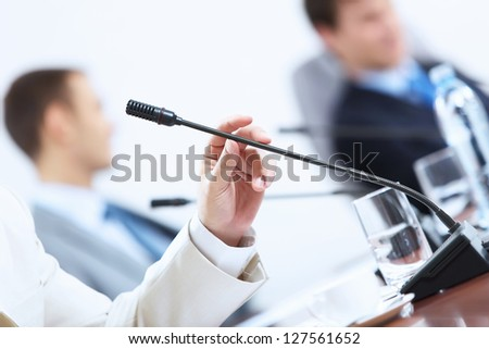 Image of businessman's hands holding microphone at conference - stock photo