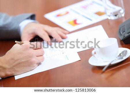 Image of businessman's hands signing documents at meeting