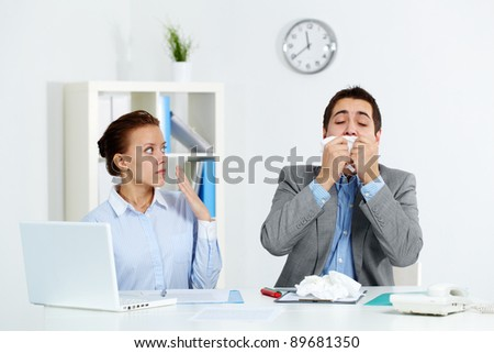 Image of businessman sneezing while his partner looking at him with anxiety in office - stock photo