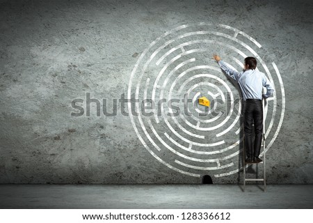 Image of businessman standing on ladder against maze picture - stock photo